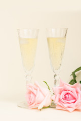 Pink blooming valentines day roses with two glasses of cold champagne