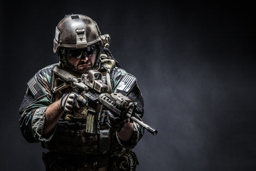 United states Marine Corps special operations command Marsoc raider with weapon. Studio shot of Marine Special Operator half-turning black background