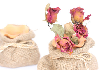Bouquet of dried withered roses in sackcloth bag on white backgr