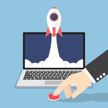 Businessman hand pushing the button to launch rocket from laptop