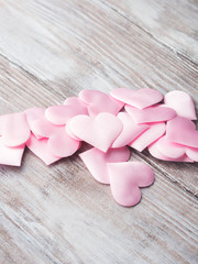 Pink hearts on textured wooden table. Valentine's mother day or baby birthday greeting card. Copy space