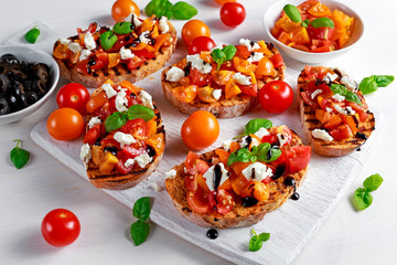 Tasty Traditional Tomato bruschetta with feta cheese topping, fresh basil and balsamic vinegar