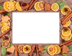 Horizontal frame composed of dried oranges, lemons, mandarins, anise stars, cinnamon sticks and on a background of brown fabric