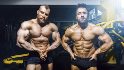 two male bodybuilder posing at the gym
