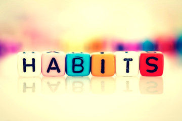 colorful word cube of habits on white background , vintage color