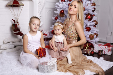 Gorgeous mother with long blond hair posing with adorable cute d