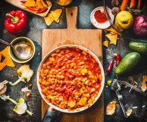 Vegetarian chili con carne dish in pan on wooden cutting board with spices and vegetables cooking ingredients on dark kitchen table background, top view. Mexican cuisine