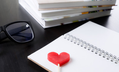 Red heart on blank book in library table