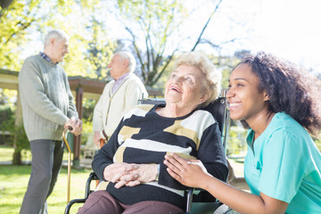 Elderdly woman on wheelchair in the garden assisted by nurse, tw