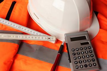 Arbeitsjacke mit Schutzhelm, Maßband, Taschenrechner und Kugelschreiber