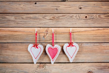 Textile hearts on old rustic wooden background.