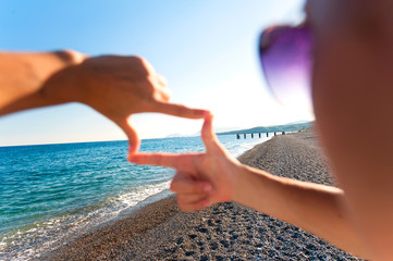 Composition finger frame- girl's hands capture spectacular seasc