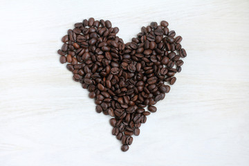 coffee concept for Dating/ a lot of coffee beans in form of heart, on a light wooden table