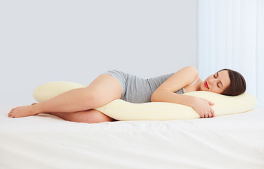beautiful pregnant woman sleeps comfortable with tummy supporting pillow