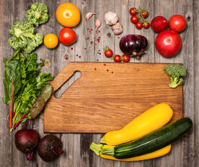 Empty cutting board and vegetables on weathered wooden background