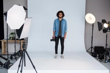 Happy male photographer standing in studio