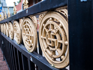 Close up on round shape railing with swastika in the middle.