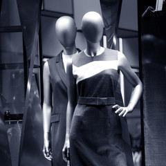Two dummy in a classic dress in the window of the female department store