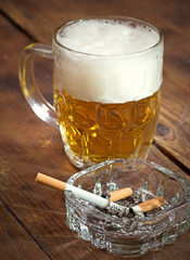 Burning cigarette in a glass ashtray and mug of beer