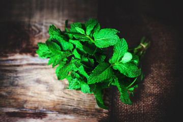 Fresh mint leaves herb on wooden table, selective focus close up