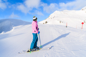 Young woman skier standing on ski slope and looking at mountains in Obertauern ski area, Austria