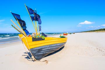 Yellow fishing boat on sandy Debki beach, Baltic Sea, Poland