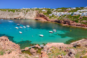 Boats anchoring in beautiful bay with crystal clear turquoise sea water, Menorca island, Spain