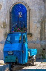 Blue Tricycle under a chapel