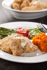 Parmesan Crusted Chicken Tenders with Roasted Sweet Potato and Roasted Asparagus topped with Campari tomatoes, Feta Cheese, Olive oil, and salt on a dark wooden background side view