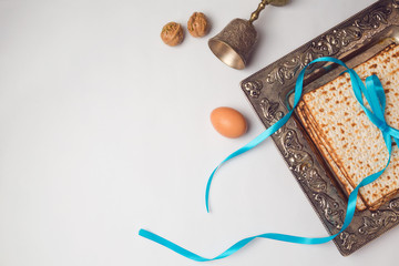Jewish holiday Passover concept with matzah, egg and wine glass on white background. View from above. Flat lay