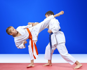Children in karategi are training the punch arm and blow leg