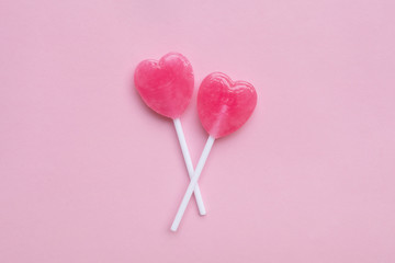 two Pink Valentine's day heart shape lollipop candy on empty pas