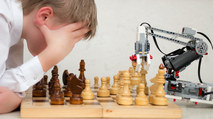Robot arm play chess with teenager. Concept. STEM education. E-learning.