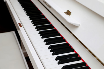 Close-up white piano, white and black keyboard