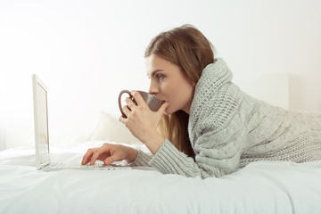 Girl using laptop and drinking coffee during break.