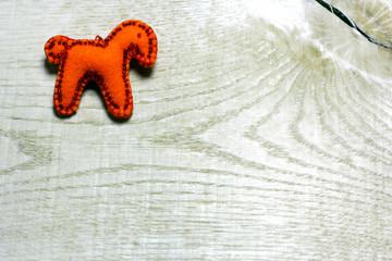 Handmade felt red color horse toy on wooden background. Concept with big copyspase for hand crafts or DIY illustration.