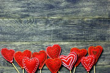 Bottom frame border of Handmade felt red color hearts on dark old wooden background. Love card for Valentine's day. Concept with big copyspase for hand crafts or DIY illustration.
