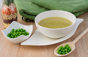 Green pea soup in a bowl with bread and sour cream