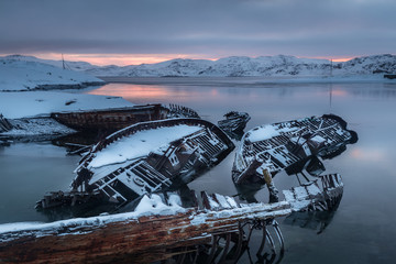 Graveyard of old ships on the shore the frozen Barents Sea