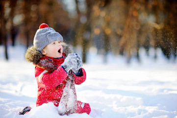Little boy in red winter clothes having fun with snow