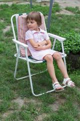 Little girl  in garden chair