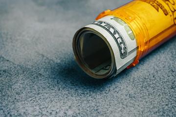Money Bills in orange pill bottle medical concept with copyspace