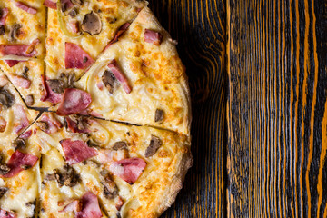 High angle view of half of delicious pizza with ham, mushrooms a