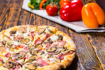 Close up of pizza near are other vegetables on a napkin on woode