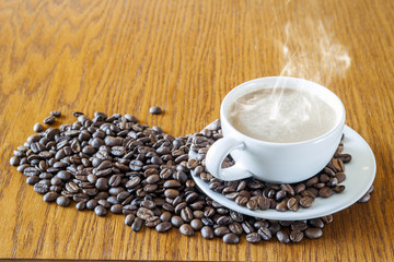 Cup of coffee in a white cup and coffee beans on wooden table ba