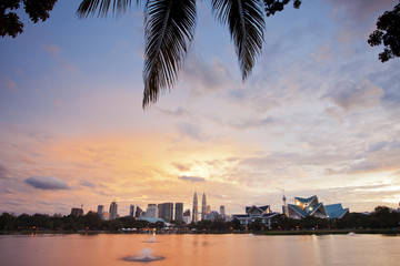 Beautiful sunset in Kuala Lumpur with palm leaves in the foreground