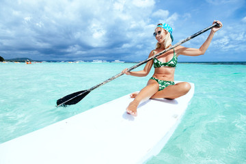 Woman floating on paddle board on the beach