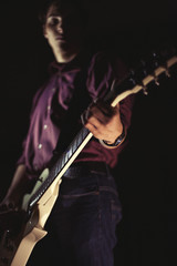 Guitarist playing electric guitar on black background