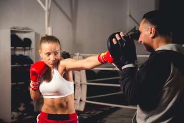 Woman boxer hitting training mitts held by her coach