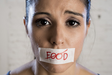 close up face of young beautiful sad latin woman with mouth sealed on stick tape with the text no food